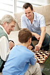 Mature man playing a chess with his son