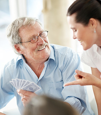 Happy woman helping an old man in playing game of card