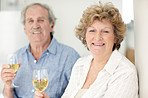 Happy old lady drinking wine with her husband