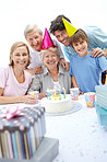 Happy old woman celebrating her birthday with her family