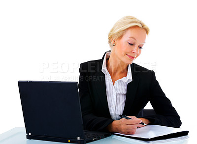 Buy stock photo Studio shot of a mature businesswoman sitting at her desk with a laptop and paperwork