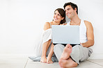 Happy young couple looking away while using laptop