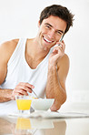 Young man talking on cell phone and having breakfast