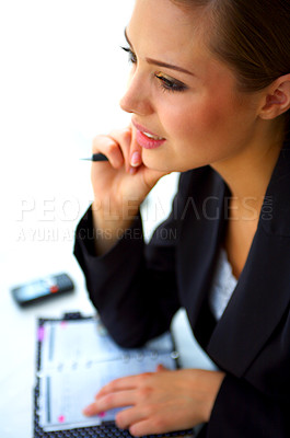 Buy stock photo Shot of a young businesswoman going through her dayplanner