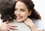 Closeup of a smiling female being hugged by a guy