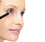 Happy woman applying eye liner to eyes