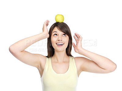 Buy stock photo Cute young lady balancing a green apple on her head - Copyspace