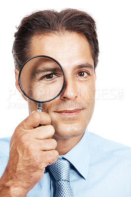 Buy stock photo Closeup portrait of a businessman looking through a magnifying glass