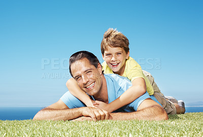 Buy stock photo Father lying on grass smiling with his son climbing on his back against clear blue sky - copyspace