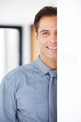 Buy stock photo Mature male business executive standing behind a wall smiling