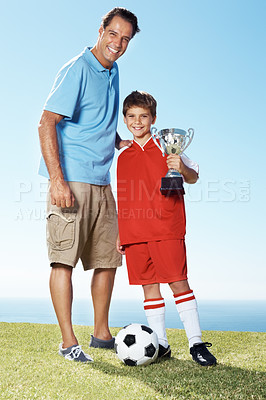 Buy stock photo Portrait of a cute little boy with his smiling father holding a winning trophy - Outdoor
