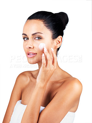 Buy stock photo Portrait of a sexy young lady applying cream on her face against white background