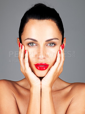 Buy stock photo Closeup portrait of a sexy young female touching her face with hands against grey background