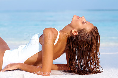 Buy stock photo Portrait of a pretty young woman having sunbath on the beach - Relaxed