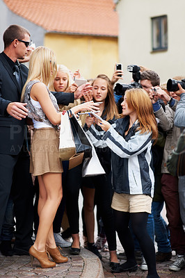 Buy stock photo Young fan asking a celebrity for her autograph