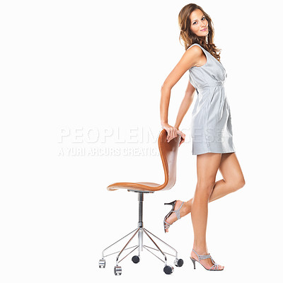 Buy stock photo Full length of beautiful young female standing with hands on chair and smiling against white background