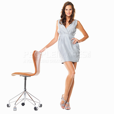 Buy stock photo Full length of young smiling female standing with hand on chair against white background