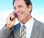 Mature business man talking on phone outside