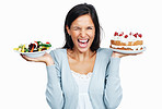 Excited woman thinking while holding cake and salad