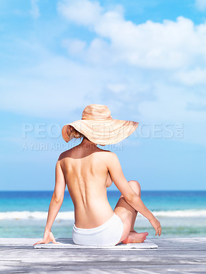 Buy stock photo Young woman wearing a hat sitting on a deck facing the ocean