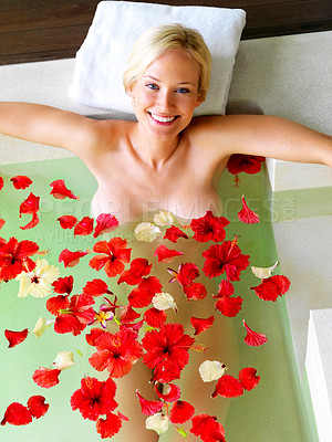 Buy stock photo Attractive young woman in a bath with floating petals