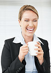 Laughing young business woman holding a cup of coffee
