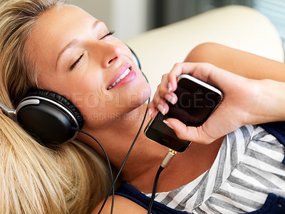 Buy stock photo Happy young lady listening to music from her mp3 player