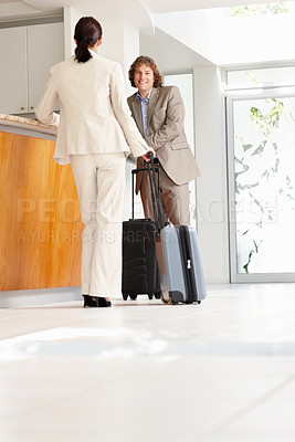 Buy stock photo Mature businessman and woman waiting at the hotel reception looking at one another