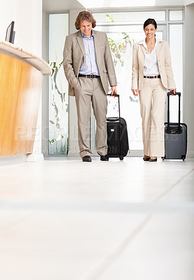 Buy stock photo Full-length of smiling mature business associates entering a hotel reception with luggage