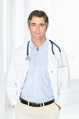 Mature male doctor standing in corridor with hands in pockets