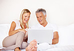Mature couple browsing internet on laptop in bedrom