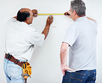 Two contractors using measuring tape to make markings on wall