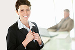 Confident middle aged business woman while colleague in blur