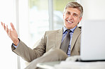 Happy mature business male with laptop at work