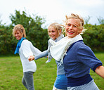 Young women holding hands and running