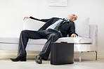Middle aged business man relaxing in sofa and suitcase on floor
