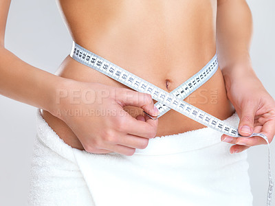 Buy stock photo Mid section of health conscious woman measuring her waist