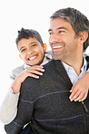 Mature man piggybacking his excited son over white background