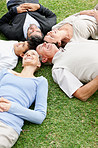 Happy relaxed multi generational family lying on grass in park