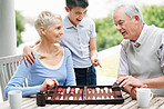 Happy boy watches elderly couple play a game of backgammon