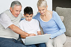 Grandparents and grandson sitting on sofa and working on laptop