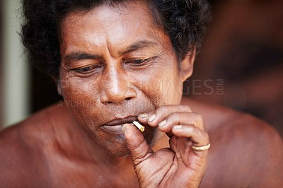 Buy stock photo Middle-aged Thai man lost in thought while smoking a cigarette