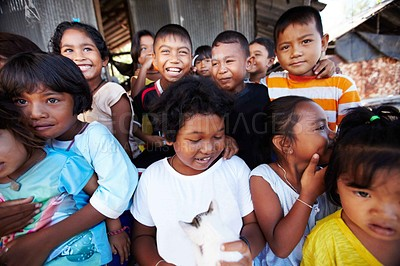 Buy stock photo A group of underprivileged children smiling and laughing grouped around a boy holding a kitten