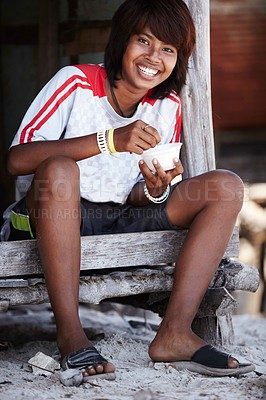 Buy stock photo Portrait of a happy looking teenage girl from rural Thailand enjoying her meal