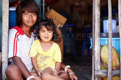 Buy stock photo An Asian teenager sitting with a little girl on her lap