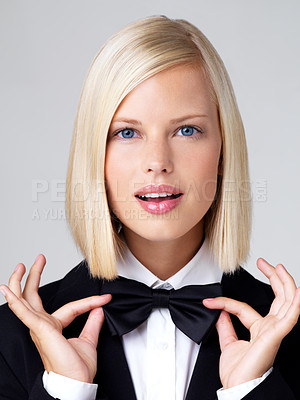 Buy stock photo Portrait of attractive young blonde looking at camera and holding on to bow tie