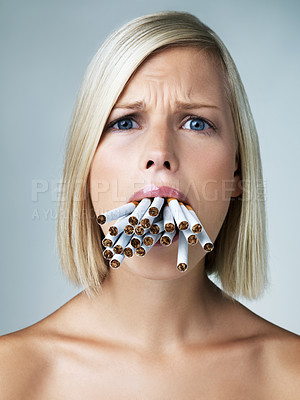 Buy stock photo Anxious young woman with a mouth filled with cigarettes
