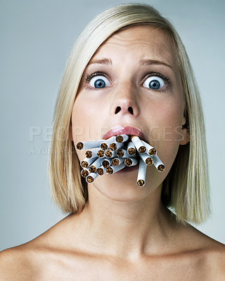 Buy stock photo Pretty young woman looking alarmed with a mouthful of cigarettes