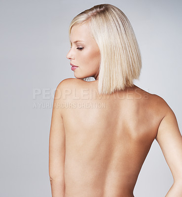 Buy stock photo Beautiful young nude woman looking over her shoulder while isolated on grey