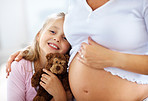 Cute young girl standing with her pregnant mother
